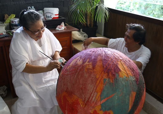 Paduka Bunda Lia Eden sedang melukis, dibantu oleh YM Agus Susilo. Her Majesty (Mother) Lia Eden is painting assisted by YM Agus Susilo.